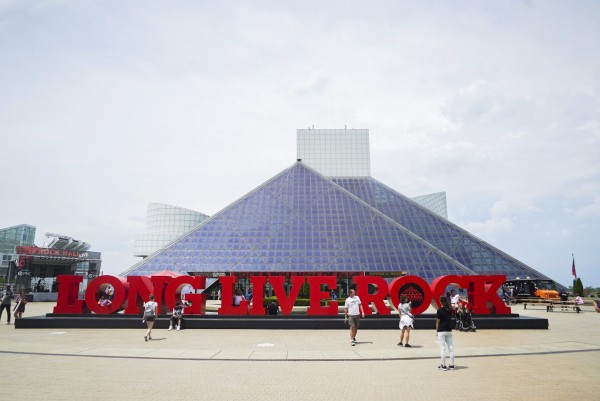"People pose for pictures outside the Rock and Roll Hall of Fame in Cleveland, Ohio, Thursday, June 29, 2017. A new exhibit called ""Power of Rock,"" opens July 1 and will give fans an taste of what it's like to be a star inducted at the Rock and Roll Hall of Fame. (AP Photo/Dake Kang)"